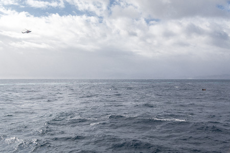 스페인어 해안 경비대 헬기는 모로코와 스페인 사이의 지중해를 건너 시도하는 난민들로 가득 뗏목을 차단 스톡 콘텐츠