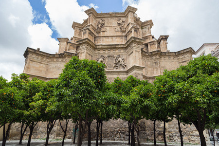 A small grove of oranges grows in front of the tall face to the monastery of St. Jerome (San Jerónimo) in Granada, Spain. Stock Photo