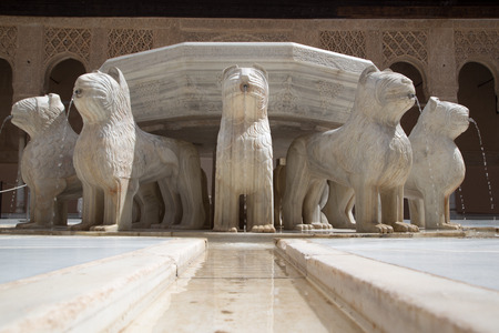 Twelve marble lions surround the fountain at the center of the Courtyard of the Lions in the Alhambra in Granada, Spain.
