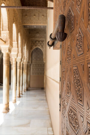 A large handle bolt lock on a carved door entering the Alhambra from the Courtyard of the Lions. Granada, Spain. Stock Photo