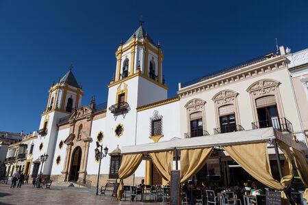 スペインは、ロンダの中心プラザ ショップ、タパスバーが立ち並んでとその 2 つの明瞭な鐘塔でソコロ教会によって片側壁します。 報道画像