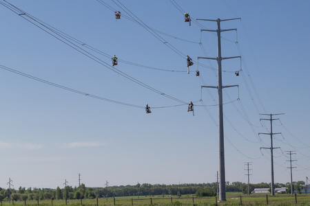 Line workers in suspended baskets inspect and install separator devices on new  electric lines transferring power to Minneapolis and Chicago. Banco de Imagens