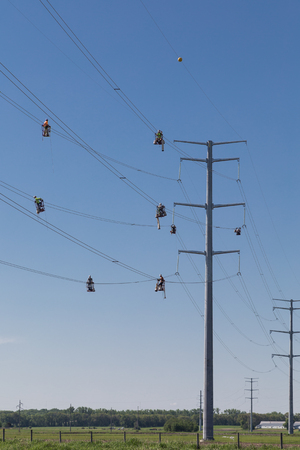 Line workers in suspended baskets inspect and install separator devices on new  electric lines transferring power to Minneapolis and Chicago. Editorial
