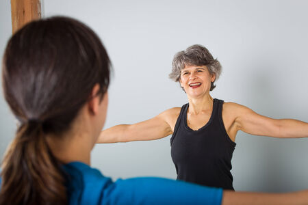 A smiling middle aged female sports trainer with outstretched arms offer class instruction. Stock Photo