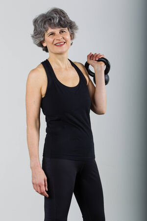 An attractive middle aged female sports trainer holds a kettle bell. Stock Photo