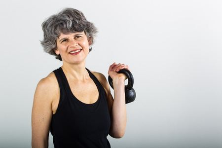 A middle aged female sports trainer holds a kettle bell.