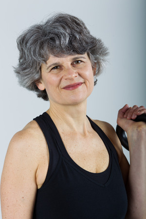 kettle bell: A middle aged female sports trainer holds a kettle bell.