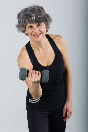 A smiling middle aged female sports trainer demonstrates use of a dumbbell.