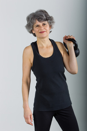A muscular middle aged female sports trainer holds a kettle bell.