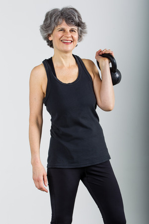 A smiling middle aged female sports trainer holds a kettle bell.