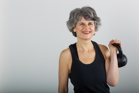 A muscular middle aged female sports trainer holds a kettle bell  Stock Photo