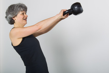 A smiling middle aged female sports trainer with gray hair demonstrates how to properly swing a kettle bell weight