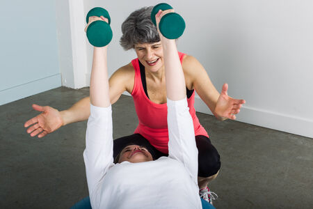 A smiling middle aged female sports trainer with gray hair demonstrates proper dumbbell press form with an athlete.
