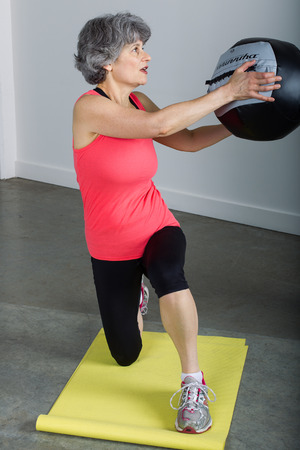 A middle aged female sports trainer with gray hair demonstrates proper use of a medicine ball.