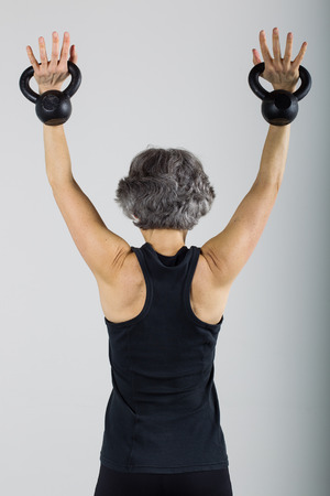 A middle aged female sports trainer does an overhead press with kettle bells.