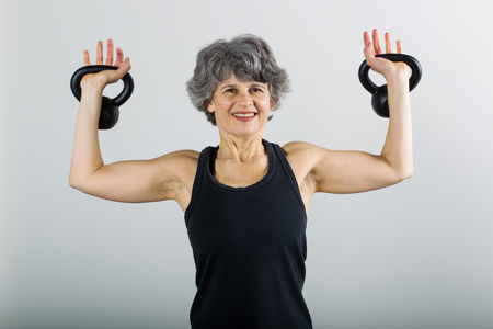 A smiling middle aged female sports trainer demonstrates the use of kettle bells. Stock Photo