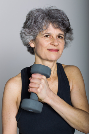 A middle aged female sports trainer demonstrates holds a dumbbell.