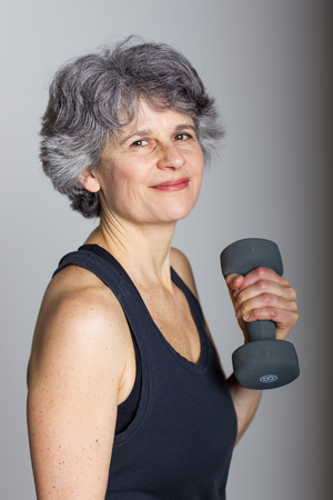 An attractive middle aged female sports trainer demonstrates holds a dumbbell.