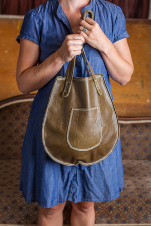 A woman in a blue cotton dress holds a green leather purse in front of her