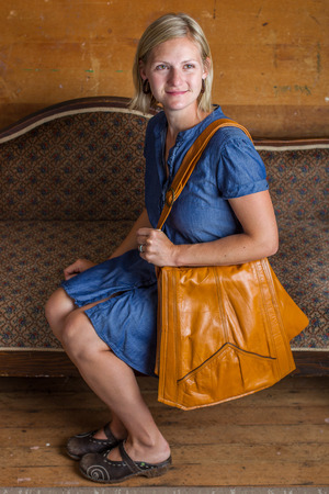 A blonde woman with blue dress and light brown purse sits on an antique couch  Stock Photo