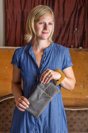 A blonde woman in a blue cotton dress holds a gray leather clutch in front of her