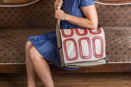 A woman with a blue dress and cream and red patterned courier bag sits on an antique couch