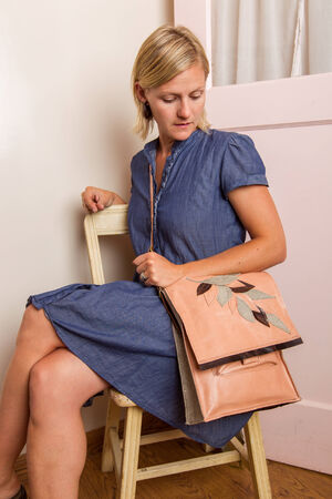 A blonde woman in a blue cotton dress wearing a pink leather purse