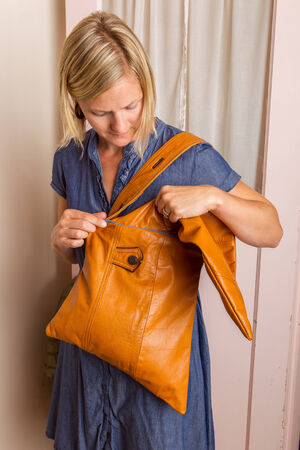 A blonde woman wearing a blue dress looks into a light brown purse