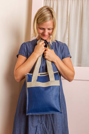 A blonde woman in a blue cotton dress holds a blue leather purse in front of her  Stock Photo