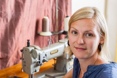Pretty blonde woman sits in front of a commercial sewing machine