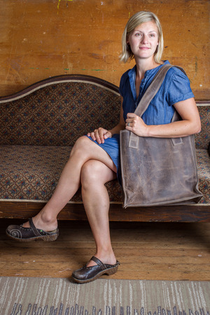 A blonde woman with blue dress and brown purse sits on an antique couch