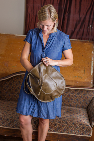 A blonde woman in a blue cotton dress looks inside a green leather purse