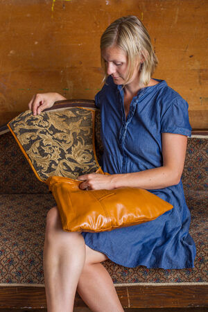 A blonde woman with blue dress looks into a light brown purse sits on an antique couch