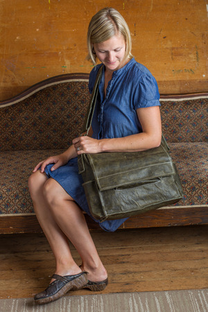 A blonde woman with blue dress and green leather courier bag sits on an antique couch