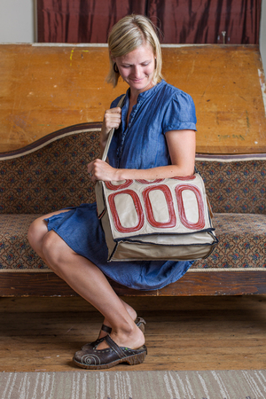 A blonde woman with a blue dress and cream and red patterned courier bag sits on an antique couch  Stock Photo