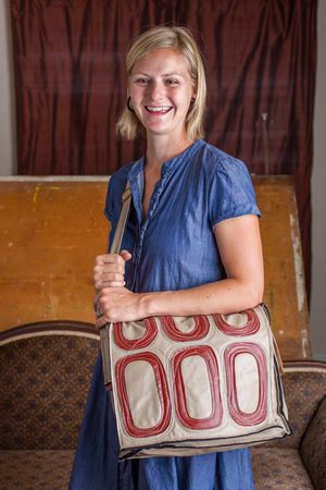 A smiling blonde woman with a blue dress wears a cream and red patterned courier bag  Stock Photo