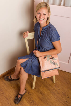 Smiling blonde woman in a blue cotton dress wearing a pink leather purse