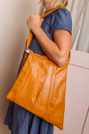 A woman wearing a blue dress holds a light brown purse  Stock Photo