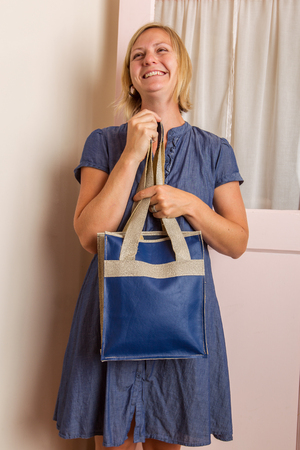A smiling blonde woman in a blue cotton dress holds a blue leather purse in front of her