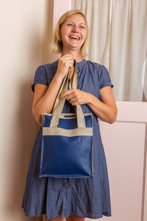 A laughing blonde woman in a blue cotton dress holds a blue leather purse in front of her  Stock Photo