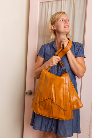 A blonde woman wearing a blue dress with a light brown purse  Stock Photo