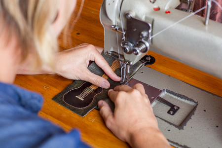 A woman sews a guitar wallet made out of reclaimed leather