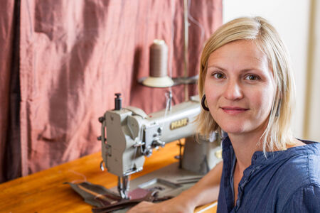 Smiling blonde woman sits in front of a commercial sewing machine