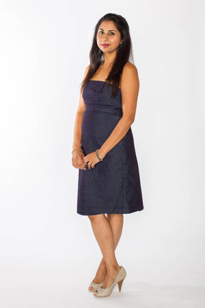 A pretty Indian woman in a blue dress and tan heels poses against a white background  Stock Photo