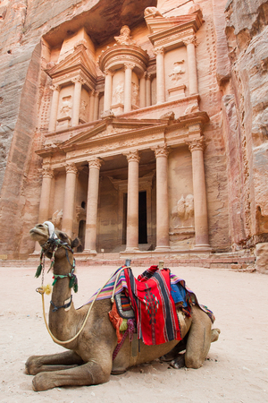 A camel rests outside  The Treasury  near the entrance of Petra, Jordan  The site was made famous in the movie  Indiana Jones and the Last Crusade    On assignment for the Jordanian Tourism Board   Stock Photo