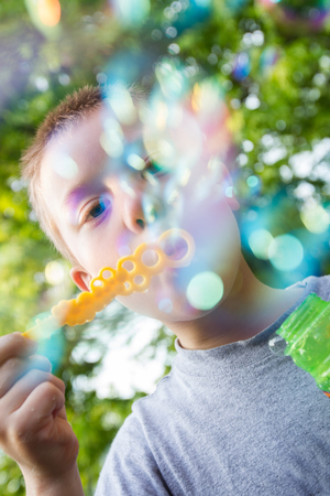 A young blond boy blows bubbles