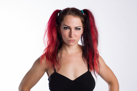 Angry punk girl with serious look and red dyed hair against a white background