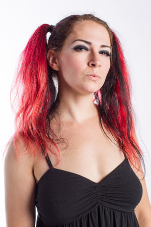 Punk girl with serious look and red dyed hair against a white background
