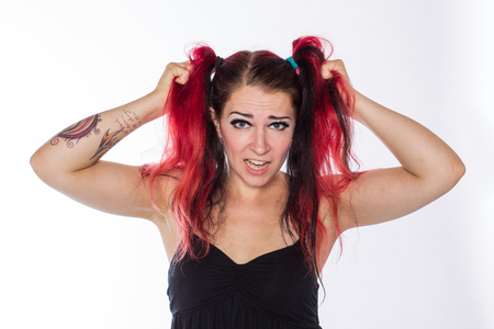 Frustrated punk girl pulls her red dyed hair against a white background