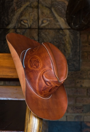 barstool: Leather cowboy hat hanging on a barstool Stock Photo